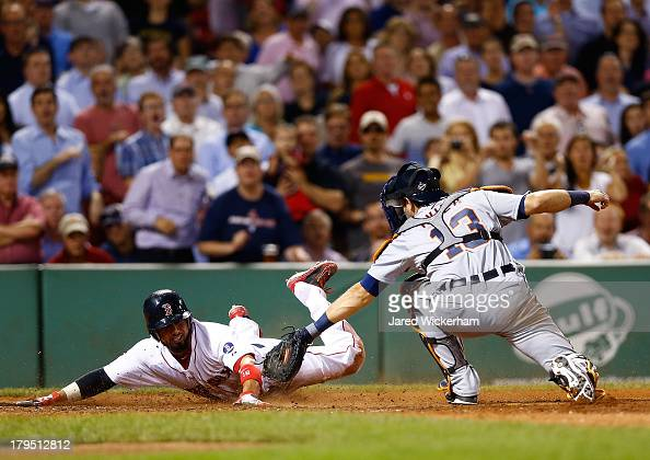 Shane Victorino of the Boston Red Sox slides safely into home plate past Alex Avila of the Detroit Tigers on a sacrifice fly in the fifth inning...
