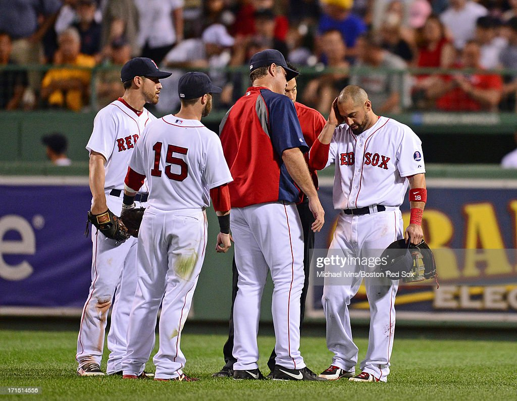 Shane Victorino #16 of the Boston Red Sox talks with manager John Farrell #53, Jacoby Ellsbury #2 and Dustin Pedroia #15 after injuring himself on a fly ball against the Colorado Rockies in the seventh inning on June 25, 2013 at Fenway Park in Boston, Massachusetts.