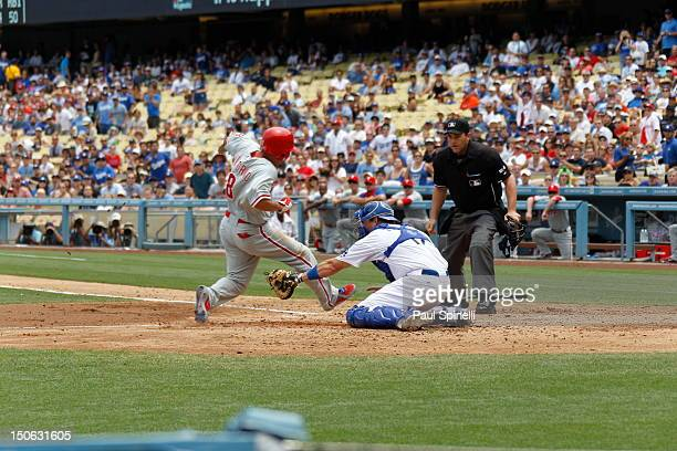 Shane Victorino of the Philadelphia Phillies avoids the tag by Matt Treanor of the Los Angeles Dodgers during the game between the Philadelphia...