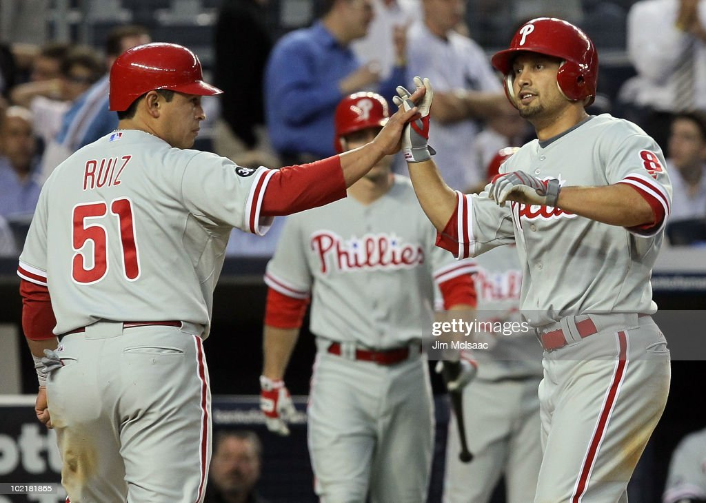 Shane Victorino of the Philadelphia Phillies celebrates his fifth inning two run home run against the New York Yankees with teammate Carlos Ruiz on...