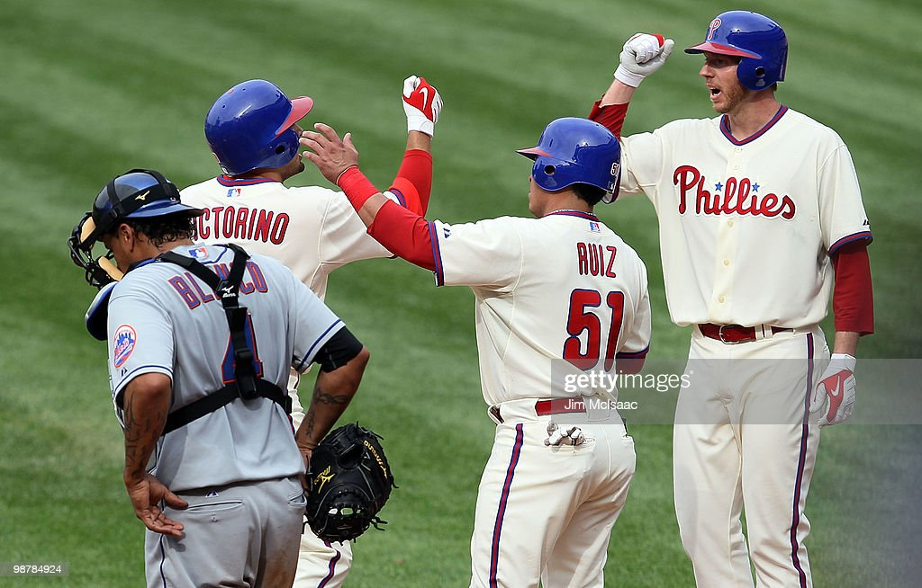 Shane Victorino of the Philadelphia Phillies celebrates his fourth inning three run home run with teammates Carlos Ruiz and Roy Halladay as Henry...