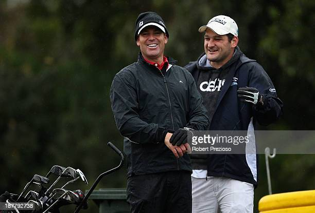 Shane Warne and Brendan Fevola prepare to play their shots on the 3rd hole during the Pro Am ahead of the 2013 Australian Masters at Royal Melbourne...