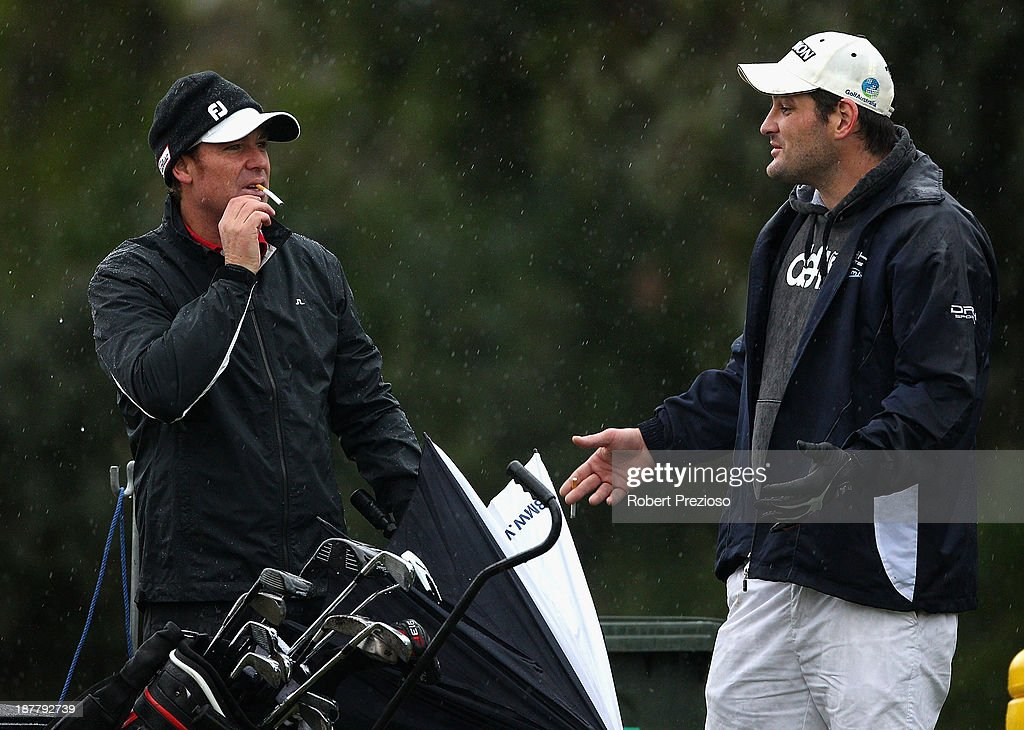 Shane Warne and Brendan Fevola prepare to play their shots on the 3rd hole during the Pro Am ahead of the 2013 Australian Masters at Royal Melbourne Golf Course on November 13, 2013 in Melbourne, Australia.