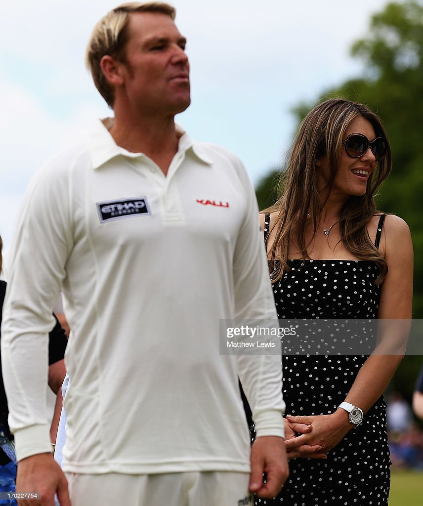 Shane Warne and Elizabeth Hurley look on during the Shane Warne's Australia vs Michael Vaughan's England T20 match at Circenster Cricket Club on June 9, 2013 in Cirencester, England.