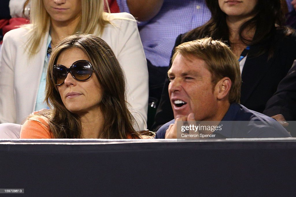 Shane Warne and Liz Hurley watch the men's third round match between Roger Federer of Switzerland and Bernard Tomic of Australia during day six of the 2013 Australian Open at Melbourne Park on January 19, 2013 in Melbourne, Australia.