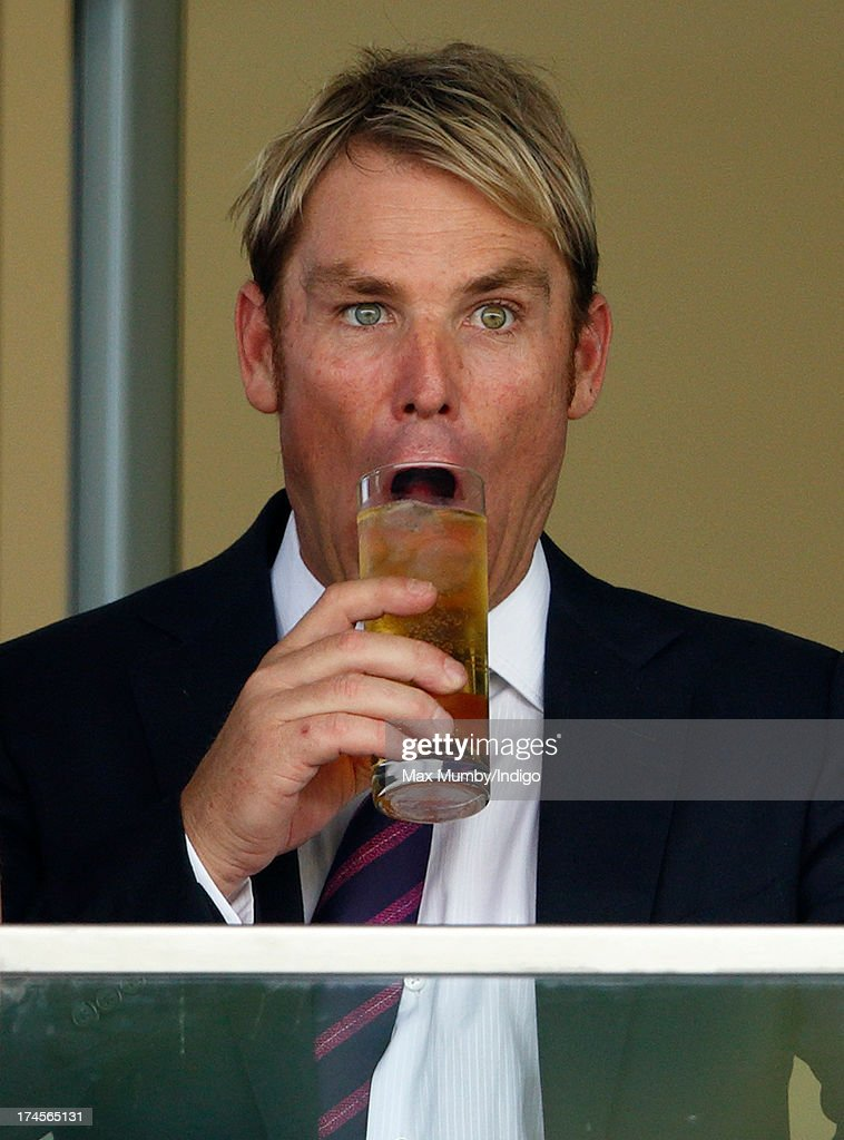 Shane Warne fools around with his glass of drink as he and Elizabeth Hurley attend the Betfair Weekend, featuring the King George VI and Queen Elizabeth Stakes, at Ascot Racecourse on July 27, 2013 in Ascot, England.