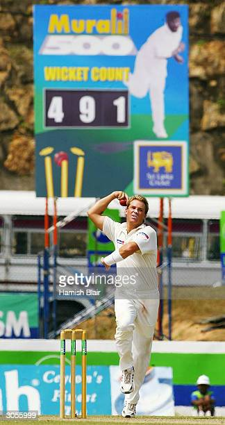Shane Warne of Australia bowls under a sign counting down his rival spinner Muttiah Muralitharan of Sri Lanka to 500 wickets Warne himself currently...