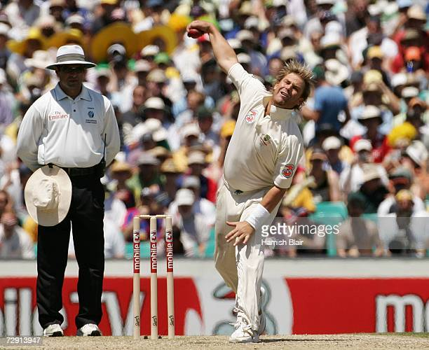 Shane Warne of Australia bowls watched by umpire Aleem Dar during day two of the fifth Ashes Test Match between Australia and England at the Sydney...