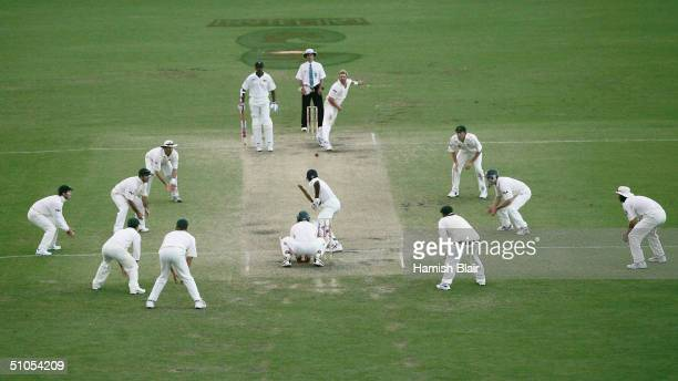 Shane Warne of Australia bowls with every fieldsman around the bat in his final over of the match during day five of the Second Test between...