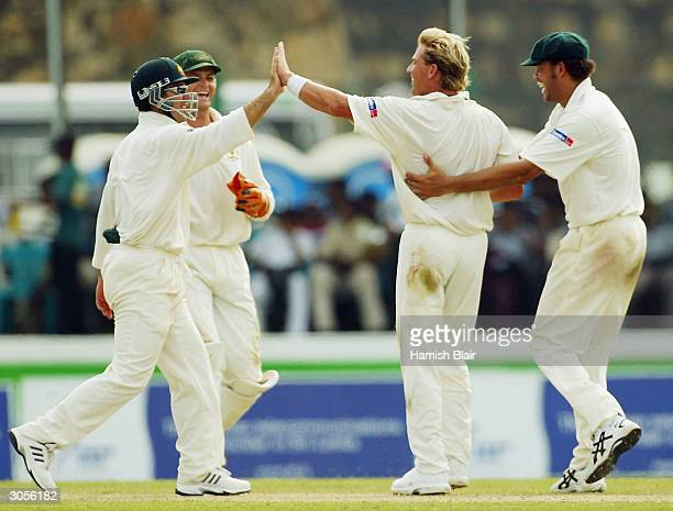 Shane Warne of Australia celebrates the wicket of Hashan Tillakaratne of Sri Lanka with team mates during day two of the First Test between Australia...