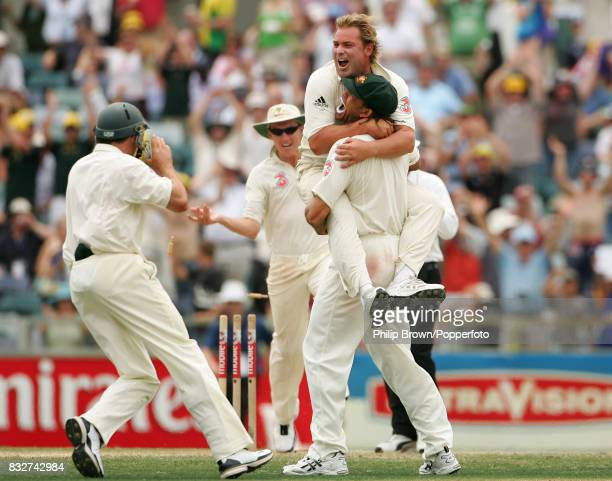 Shane Warne of Australia celebrates with Andrew Symonds and Michael Hussey after taking the final wicket of the match to win the 3rd Test between...