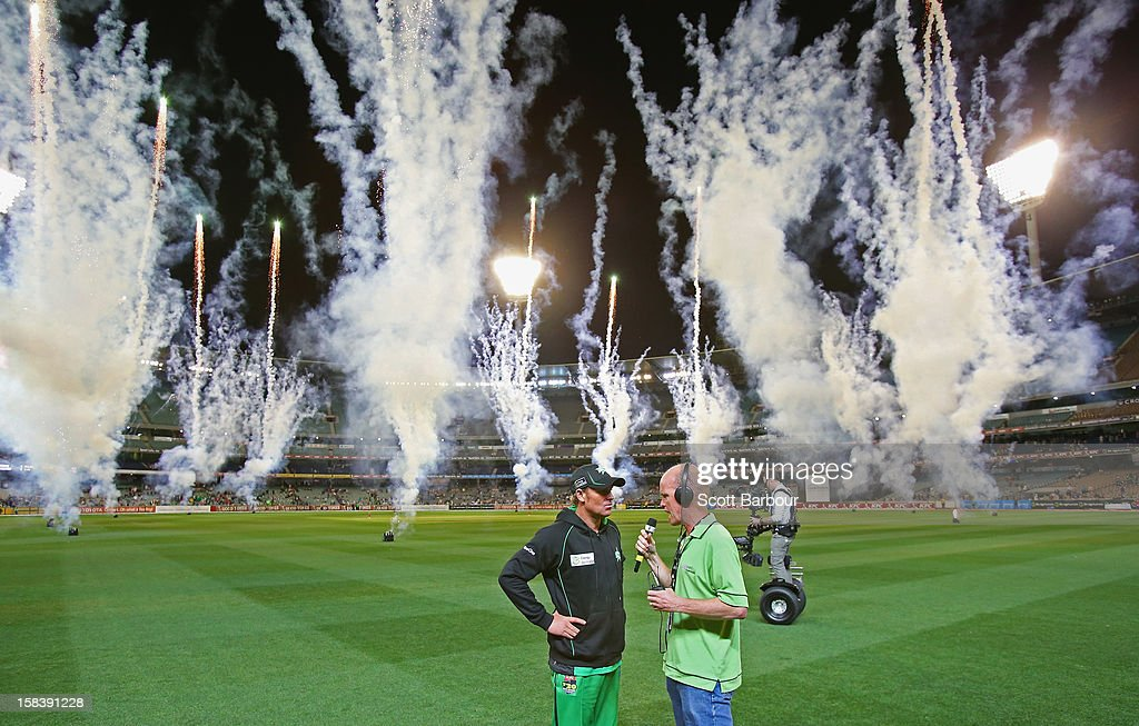 Shane Warne of the Stars is interviewed by Dan Lonergan as fireworks explode after the Big Bash League match between the Melbourne Stars and the Hobart Hurricanes at the Melbourne Cricket Ground on December 15, 2012 in Melbourne, Australia.