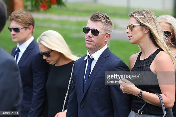 Shane Watson and wife Lee Furlong and David Warner and fiancee Candice Falzon walk in the funeral procession down Wallace Street Macksville after the...