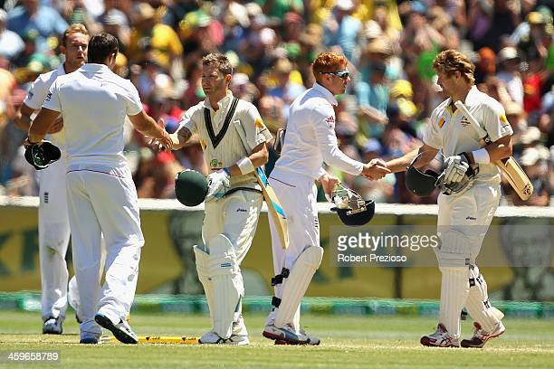 Shane Watson of Australia and Michael Clarke of Australia shake hands with England players after winning the match during day four of the Fourth...