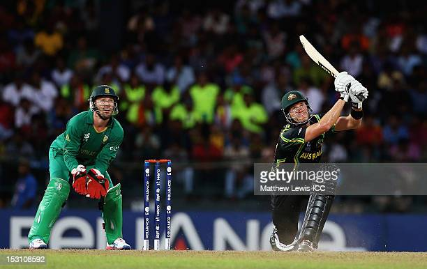 Shane Watson of Australia hits the ball towards the boundary as AB de Villiers of South Africa looks on during the ICC World Twenty20 2012 Super...