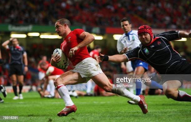 Shane Williams of Wales evades the tackle of Tatsukichi Nishiura of Japan to score a try during the Rugby World Cup 2007 Pool B match between Wales...