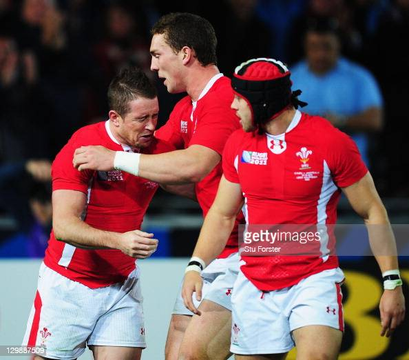 Shane Williams of Wales is congratulated by teammates George North and Leigh Halfpenny after scoring their first try during the 2011 IRB Rugby World...