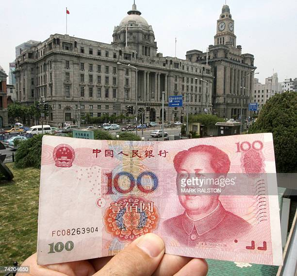 A Chinese 100 renminbi note held up in front of old bank buildings on the historic bund area of Shanghai 21 May 2007 China recently said that it will...