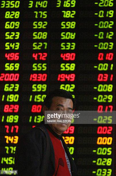A Chinese investor in front of a stock price board at a private securities firm in Shanghai 23 March 2007 Chinese share prices posted record gains 22...
