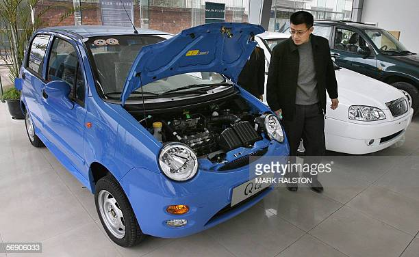A customer looks at the engine of a Chery QQ car at a dealership of China's largest car exporter Chery Automobile in Shanghai 22 February 2006 The...