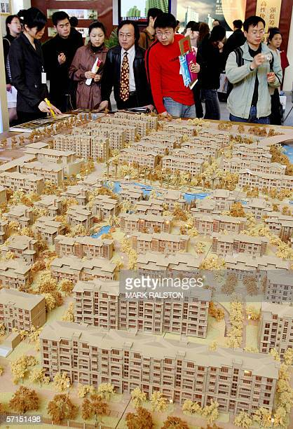 A group of potential real estate buyers look at an estate plan by a local developer at a property exhibition in Shanghai 19 March 2006 Signs of a...