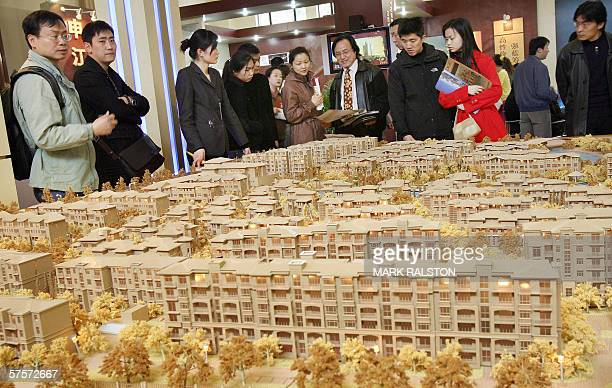 A group of potential real estate buyers look at an estate plan by a local developer at a property exhibition in Shanghai 19 March 2006 One of the...