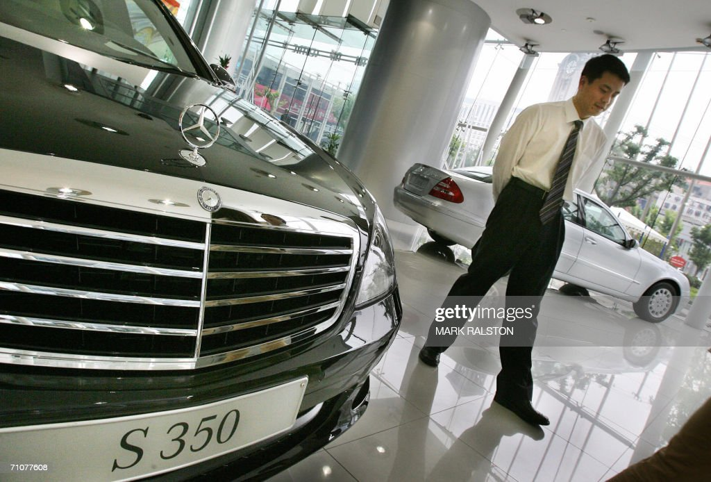 A salesman walks past a Mercedes Sclass sedan at a showroom in Shanghai after the firm announced a 57 percent increase in car sales in China and Hong...