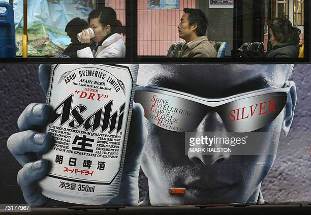 Bus passengers sit above an ad for Asahi Beer in Shanghai 02 February 2007 Japan's Asahi Breweries Ltd is currently building a plant in China's...