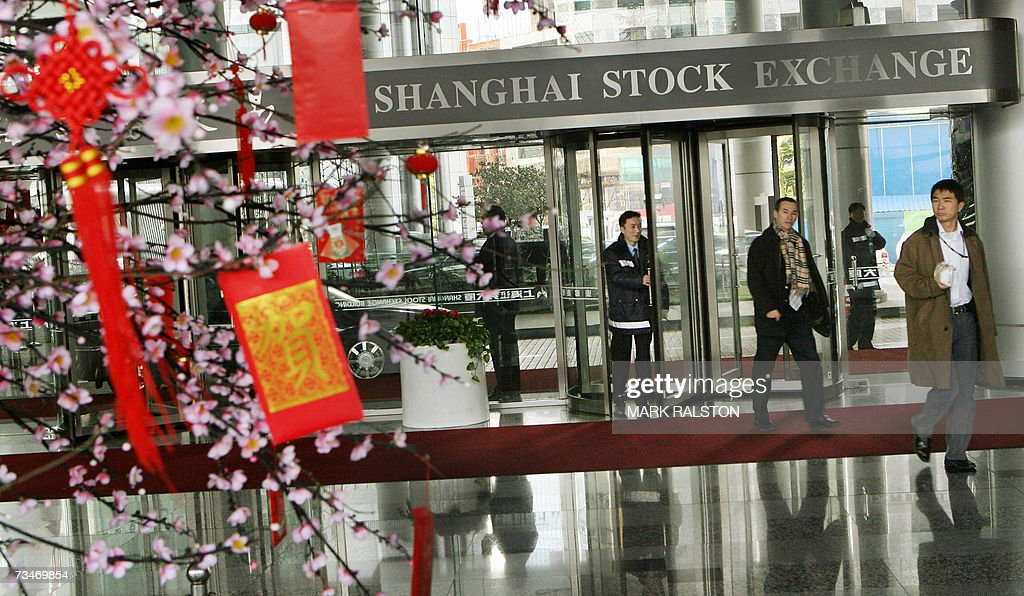 Chinese investors arrive at the Shanghai Stock Exchange as they pass near a blossom tree containing traditional red envelopes containing money for good luck in Shanghai 28 February 2007. The dramatic one-day wobble in Chinese share prices highlights the tricky task facing regulators as they try to prevent a dangerous bubble in a market that has grown 130 percent in a year. Analysts said that the 27 February 8.84-percent plunge in the Shanghai Composite Index suggested the government may have miscalculated, the sell-off was also partly caused by profit taking after a long period of gains. AFP PHOTO/Mark RALSTON