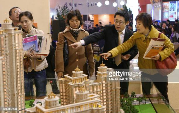 Chinese investors talk with a property salesman for a new housing development at a real estate exhibition in Shanghai 16 March 2007 China's...