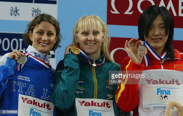 Jessicah Schipper from Australia holds up her gold medal for winning the Womens 200 metre butterfly final in a time of 20511 next to second place...