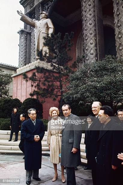 Premier Chou EnLai Mrs Pat Nixon President Richard Nixon and Secretary of State William P Rogers pause outside the Shanghai Exhibition Hall under a...