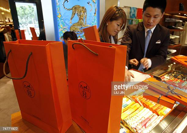Salespeople pack goods for customers at an outlet of the French fashion brand Hermes in Shanghai 19 June 2007 The luxury icon opened a new store to...