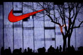 Shanghai residents pass by a Nike store on the Nanjing Road shopping street on April 17 2010 in Shanghai China The Shanghai World Expo will be held...