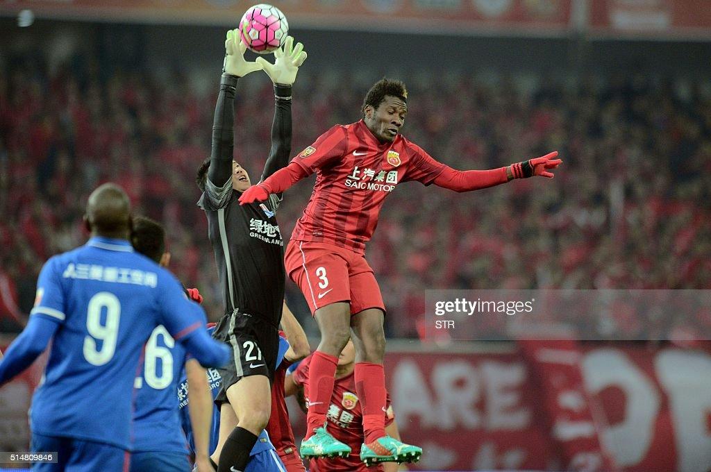 Shanghai Shenhua's goalkeeper Li Shuai catches the ball next to Asamoah Gyan of Shanghai SIPG during their Chinese Super League football match in...