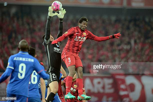 Shanghai Shenhua's goalkeeper Li Shuai catches the ball next to Asamoah Gyan of Shanghai SIPG during their Chinese Super League football match in...