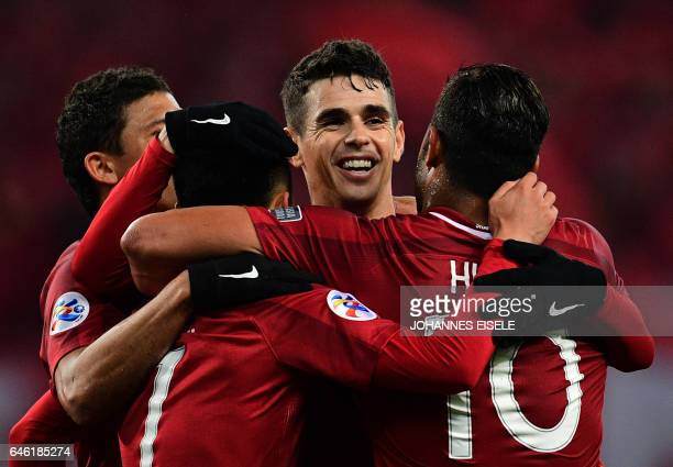 Shanghai SIPG' Brazilian midfielder Oscar celebrates with his teammates during the AFC Asian Champions League group football match between China's...