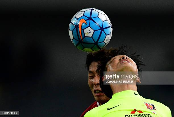 TOPSHOT Shanghai SIPG defender Zhang Wei and Urawa Red Diamonds forward Tadanari Lee fight for the ball during the AFC Asian Champions League group...