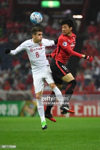 Shanghai SIPG forward Oscar and Urawa Red Diamonds midfielder Yosuke Kashiwagi compete for the ball during the AFC Champions League football match...