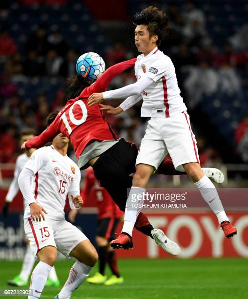 Shanghai SIPG midfielder Zhang Yi fights for the ball with Urawa Red Diamonds midfielder Yosuke Kashiwagi during the AFC Champions League football...