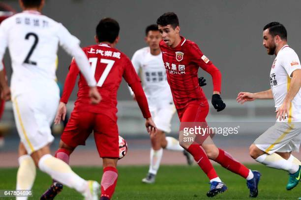 Shanghai SIPG's Brazilian midfielder Oscar fights for the ball during the Chinese Super League match against Changchun Yatai in Shanghai on March 4...