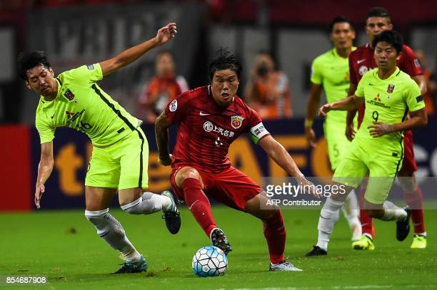 Shanghai SIPG's Cai Huikang fights for the ball against Urawa' Aoki Takuya during the AFC Champions League semifinal football match between Shanghai...
