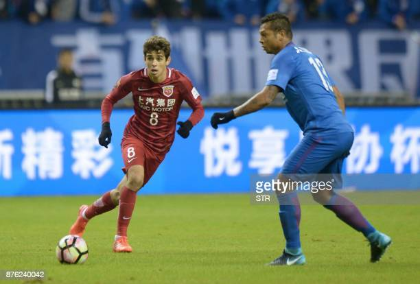 Shanghai SIPG's Oscar fights for the ball with Shanghai Shenhua's Fredy Guarin during their Chinese FA Cup football match in Shanghai on November 19...