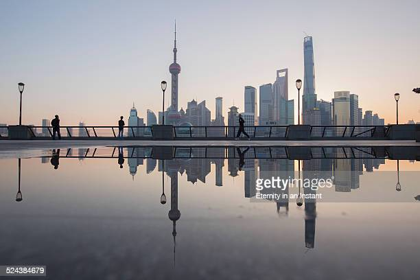 Shanghai skyline at sunrise reflected in water