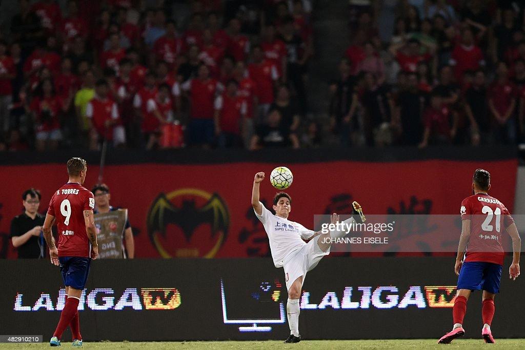 Shanghai's Argentinian forward Dario Conca kicks the ball during a friendly football match between Shanghai SIPG and Atletico Madrid in Shanghai on...