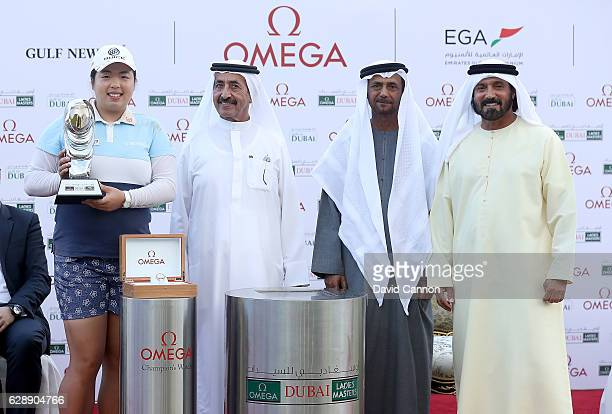 Shangshan Feng of China holds is presented with the trophy by His Highess Sheikh Hasher bin Maktoum bin Juma Al Maktoum the Director General of the...