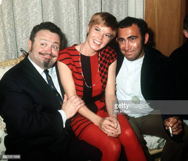 Shani Wallis sits between comedian and singer Harry Secombe and composer Lionel Bart at a party for the cast of the film 'Oliver' held at Martini...