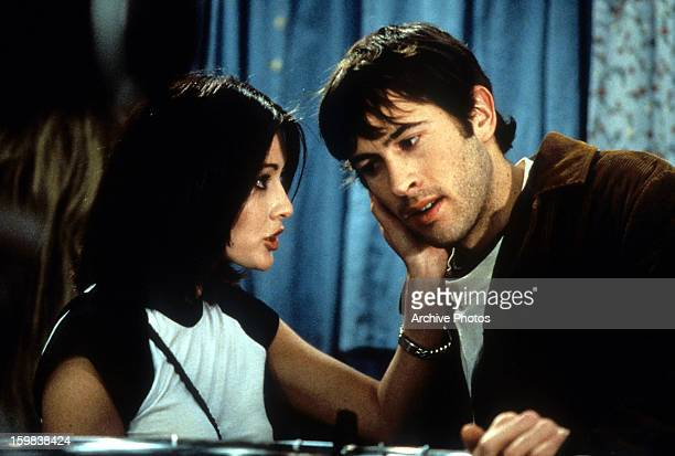 Shannen Doherty grabbing the cheek of Jason Lee in a scene from the film 'Mallrats' 1995