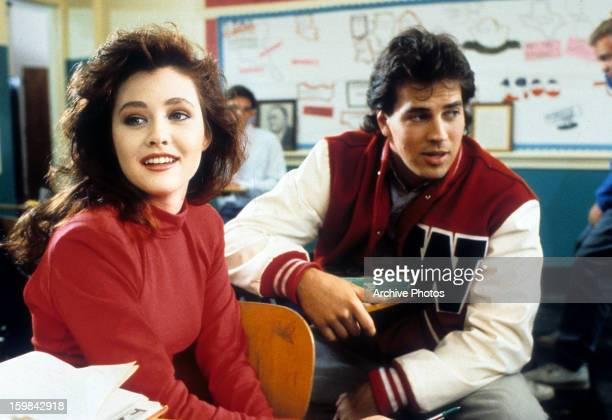 Shannen Doherty sits in front of a boy in class in a scene from the film 'Heathers' 1988