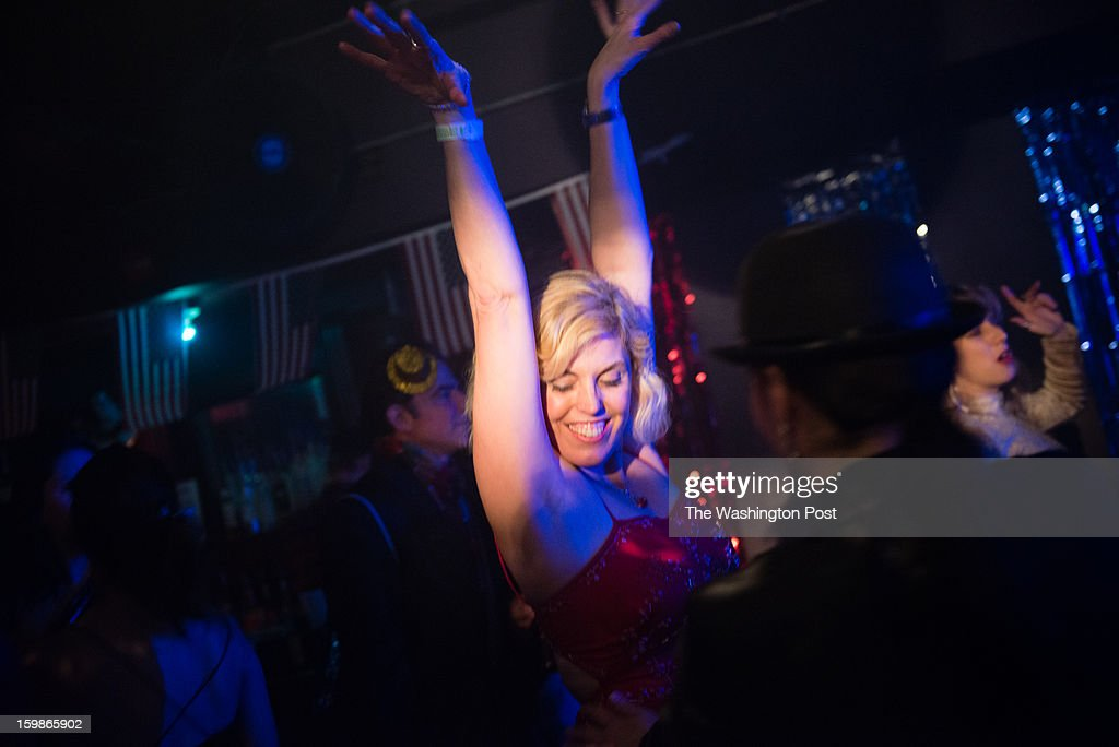 Shannon Benton, 42, of Alexandria, VA throws her arm in the air in celebration. The 2013 Artist's Inaugural Ball featured live music, fire performances, Djs, dancing, a hookah lounge and more. It was spread among six areas in the Rock and Roll Hotel and Gallery O on H. A portion of the proceeds went to local charities, Miriam's Kitchen and One Common Unity. The hosts were Mischief, Rogue Wave Project, Artomatic, and Meso Creso.